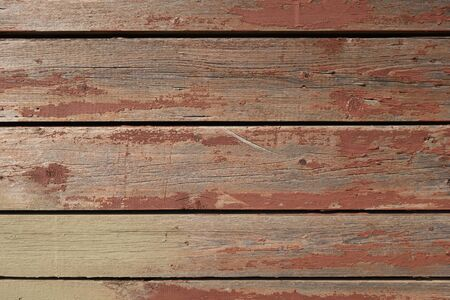 Wall of old boards with cracked red paint. Creative vintage background. Pine boards are red