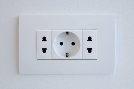 A block of white outlets consisting of one EU standard outlet with grounding and two US standard sockets Imagens