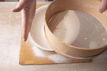 Large bowl, cutting board, sieve for sifting flour on the table. Female hands sifting flour in the home kitchen