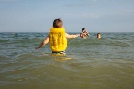 A 5 year old boy is swimming in a swimming vest with his older brother in the sea on a sunny day