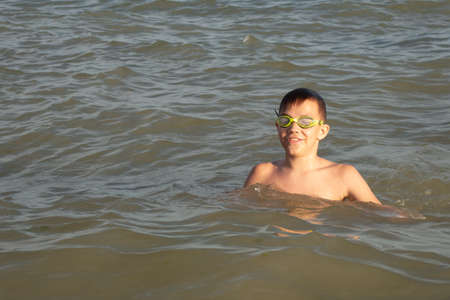 A 10-year-old boy is swimming and having fun in the sea near the shore in green swimming goggles