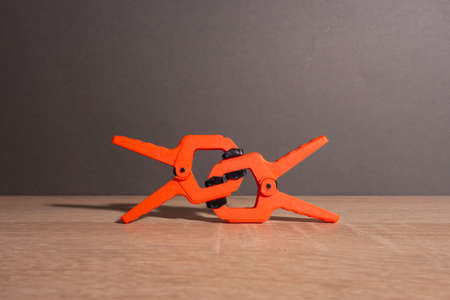 Clothespins, carpentry clamps of orange color lie on a wooden table.
