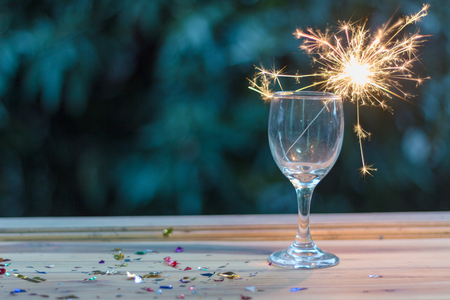 A glass of wine on a wooden table with fireworks shows the concept of celebrations on the day. Banco de Imagens