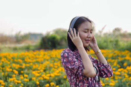 Women are listening to music with wireless headphones happily. There is light in the picture. Banco de Imagens