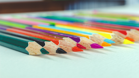 Colored pencils are placed on white paper. Stock Photo