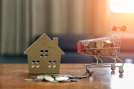 Investeringsideeën voor onroerend goed met huismodellen en munten die als medium in een winkelwagentje worden geplaatst.