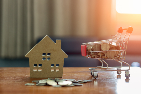 Real estate investment ideas using house models and coins placed in a shopping cart as a medium.