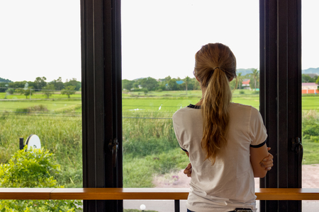 The woman stands facing the back porch, the concept of loneliness.