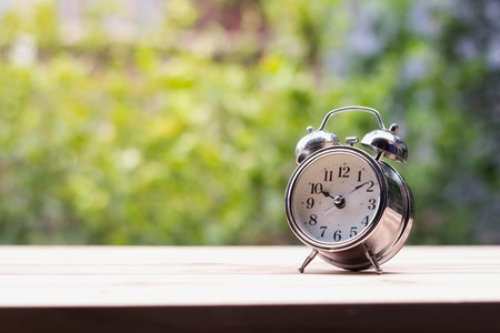 The silver desk clock rests on a wooden table with a blurry background.