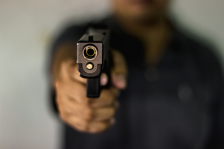 A man holding a gun pointing to a target demonstrates the violence of a gun with blurry background