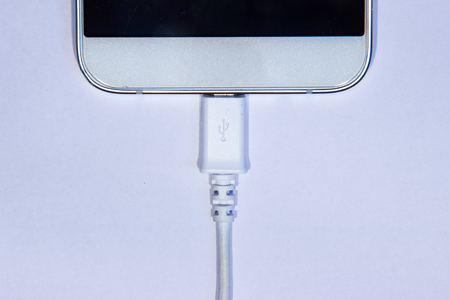 Cell phone plugged in data transfer cable on a white background.