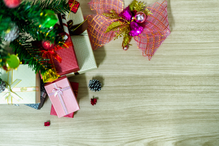 The top view of the pink gift box rests beneath a green fir that is decorated for a Christmas holiday in the winter season, which is placed on a wooden texture table. 写真素材