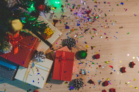 The top view of the red gift box rests beneath a green fir that is decorated for a Christmas holiday in the winter season, which is placed on a wooden texture table. 写真素材