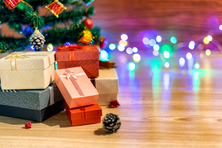 the pink gift box rests beneath a green fir that is decorated for a Christmas holiday in the winter season, which is placed on a wooden texture table.