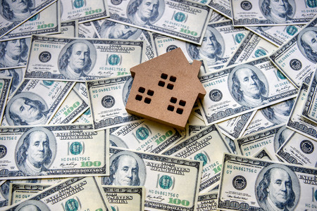 Top view of financial investment concept with real estate business for growth to gain profit And residential with a house model placed on the background of dollar banknotes currency