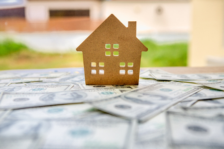 financial of investment concept with real estate business for growth to gain profit And residential with a house model placed on the background of dollar banknotes currency 写真素材