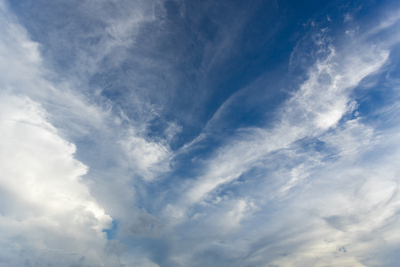 White cirrus clouds in the blue sky on a clear day in the summer. Used as a background image.