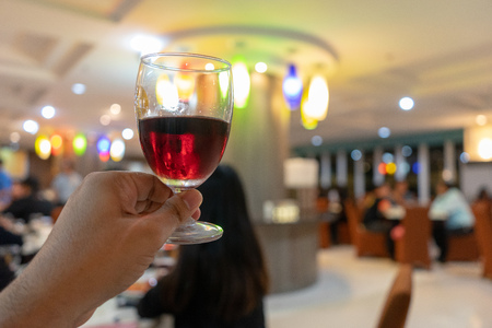 The male hand is holding a glass of wine with a drink in celebration with people in the event that enjoys a holiday lifestyle in a romantic atmosphere.
