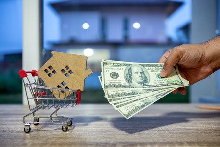 hand a businessman Investing and saving money or borrowing money from financial institutions to buy home for the future is a valuable asset in the concept of house model coupled with dollar banknotes.