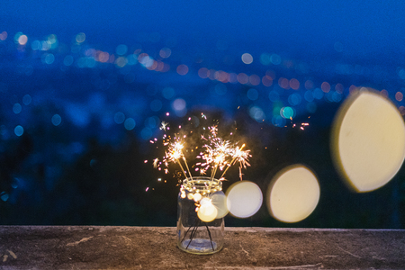 Glass dozen on the floor, with colorful fireworks on the side during the Twilight period, bokeh background on the holiday happiness concept. 写真素材