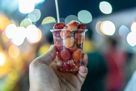 Mans hand holding Strawberry cone for eating on holidays summer. There is a bokeh background.