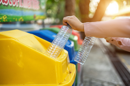 Separating waste plastic bottles into recycling bins is to protect the environment, causing no pollution, reduce global warming, helping to balance the ecology. It is  environmentally friendly action. 写真素材