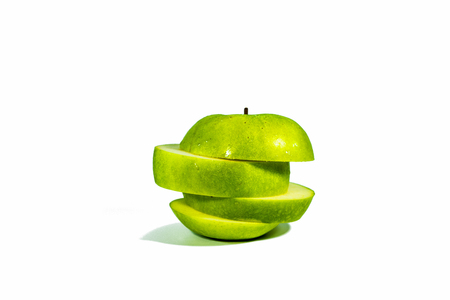 Sliced green apples, stacked isolated on a white background