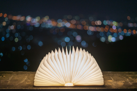 A book that opens with light on a paper like magic, placed on a cement floor with a bokeh background for Christmas. In the concept of dreams and imagination 写真素材