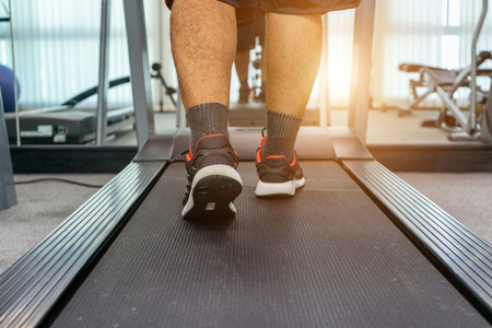 Men are exercising by running on a treadmill after working in an activity indoor fitness center as a healthy body. concept sport run for wellness.