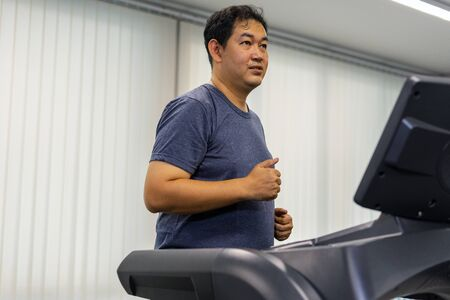 Male adult athletes are running on the equipment right machine treadmill are an indoor exercise at the gym after work, making the body healthy and happy.