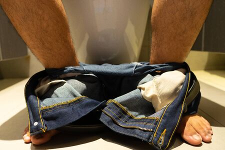 Mens legs take off jeans, sit in the bathroom.