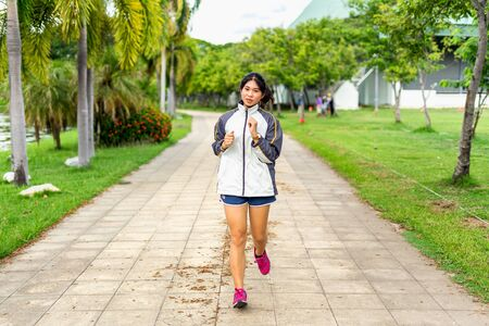Women exercising in the morning happily with running sports in the park for health is an activity that is suitable for the lifestyle of the new generation. 写真素材