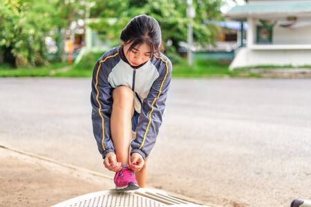 Women are tied to the shoes to prepare for the marathon. Jogging is good for health. 写真素材