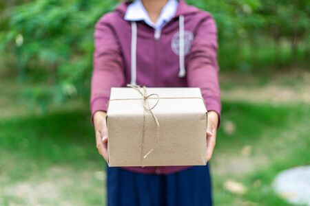 The girl's hand is giving a gift box for a special day or surprise or festival such as Christmas, New Year and Anniversary, making the recipient happy with the gift.