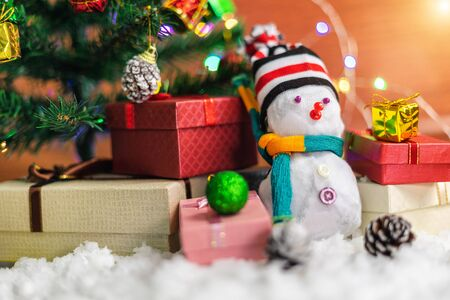 Snowman for decorating with Christmas tree with colorful gift boxes on snow ground for Christmas holiday celebration