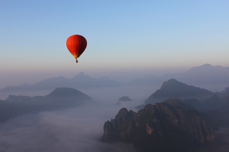 Red Hot-air Balloon float over Misty Mountain in Vang Vieng, Laos Stock Photo