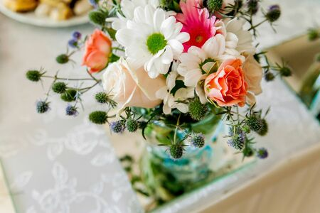 Beautiful bouquet of flowers from roses and other flowers on a light background in a glass vase