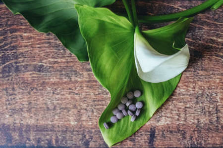 purple pills are scattered on a beautiful white flower, wooden background 版權商用圖片 - 150678476