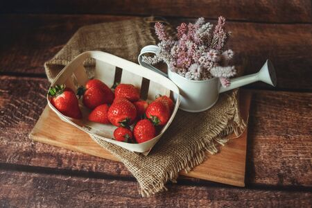 Fresh red strawberries in an eco-basket is on the table, next to it is a vase with summer wildflowers, breakfast, sunny day 版權商用圖片