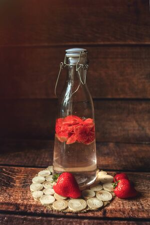 Fresh Strawberry in bottle with water, macro, dark background, toned