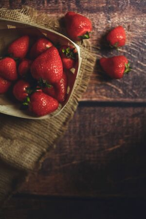 Fresh strawberries on a wooden table, eco plate, top view, dark light, early rays 版權商用圖片 - 131870746