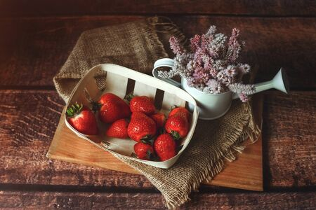 Fresh red strawberries in an eco-basket is on the table, next to it is a vase with summer wildflowers, breakfast, sunny day, toned 版權商用圖片