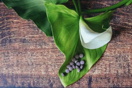 purple pills are scattered on a beautiful white flower, wooden background