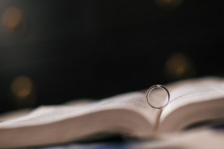 Wedding ring lies in the expanded Bible, a dark background, bokeh, macro 版權商用圖片