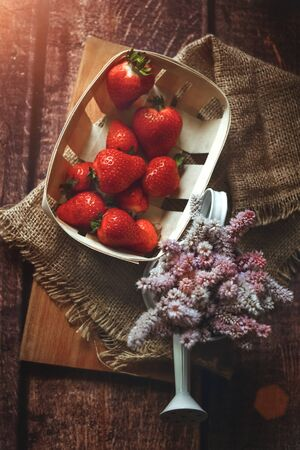 Fresh red strawberries in an eco-basket is on the table, next to it is a vase with summer wildflowers, breakfast, sunny day, shot above, eco style, toned 版權商用圖片