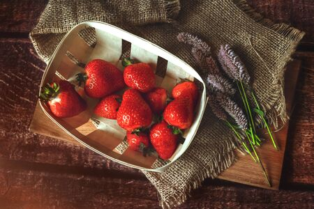 Fresh red strawberries in an eco-basket is on the table, breakfast, sunny day, shot above, eco style, toned 版權商用圖片 - 131871961