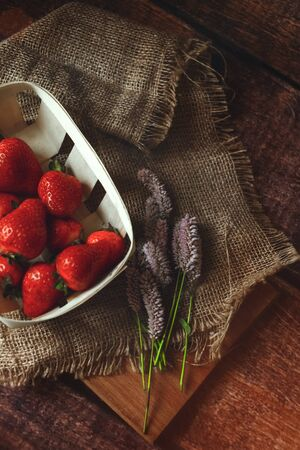 Fresh red strawberries in an eco-basket, sunny day, shot above, eco style, toned