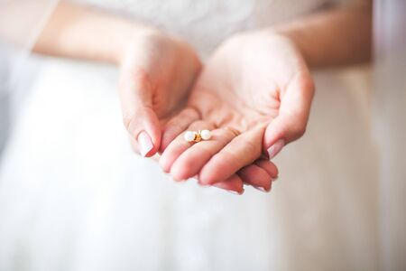 White earrings in the beautiful and gentle hands of the bride, dressed in a wedding snow-white dress