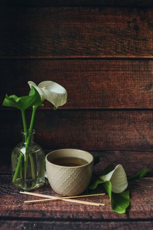 A light beige large ceramic cup stands on a dark wooden table, black hot tea is poured in it, a beautiful breakfast with an unusual white flower cal