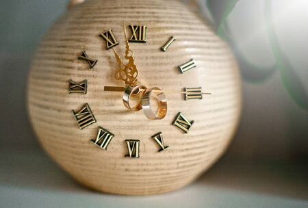 Very beautiful vintage clock with classic golden arrows, on which gold wedding rings are visible, on a light background